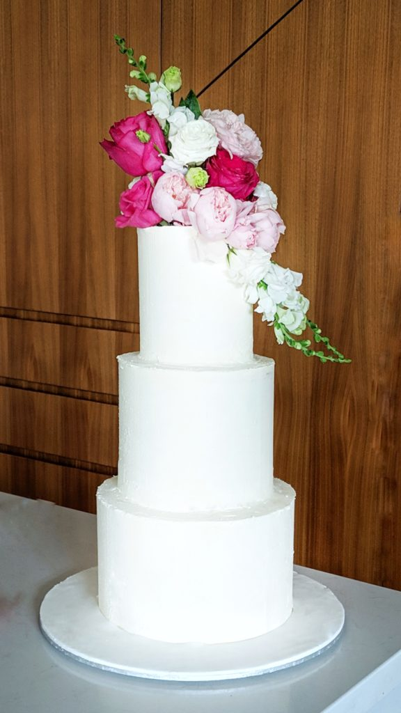 3 tier white buttercream wedding cake with fresh flowers