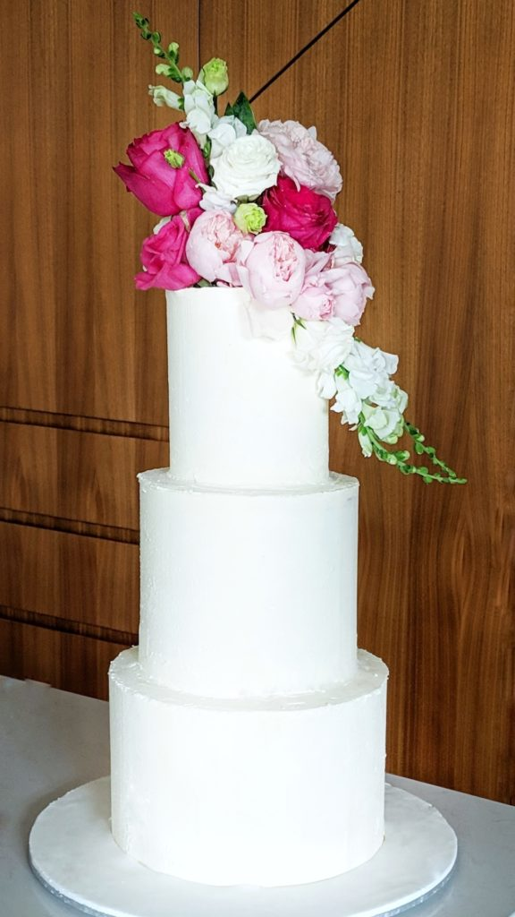 3 tiered buttercream wedding cake with fresh roses