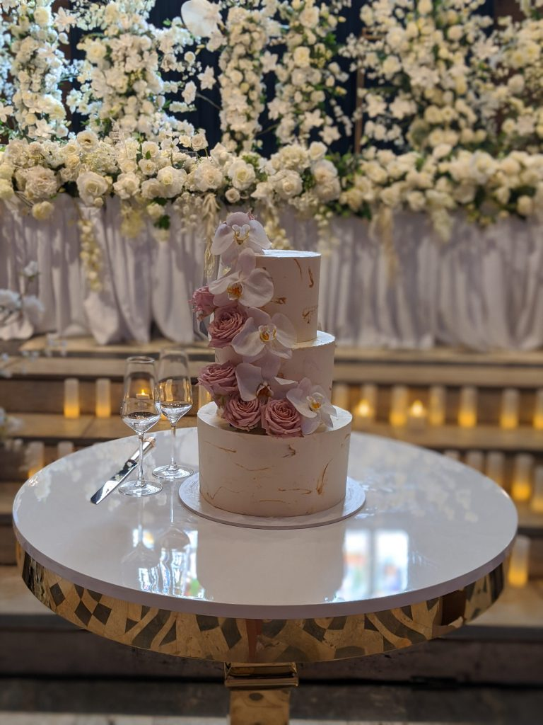 3 tiered buttercream wedding cake with fresh orchids