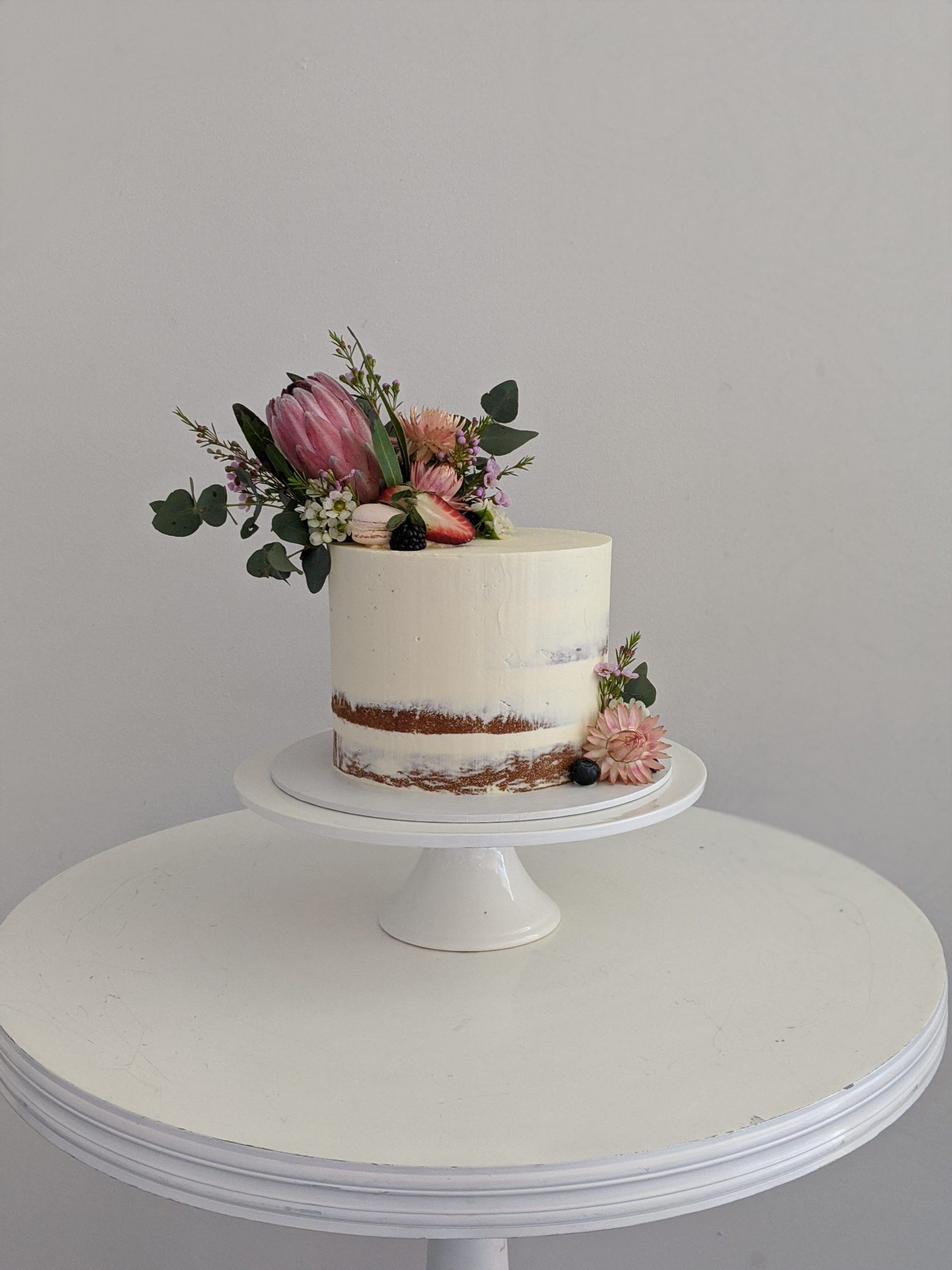 rustic semi naked buttercream wedding cake with native flowers