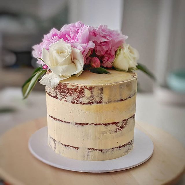 Semi naked cake with salted caramel buttercream, peonies and roses