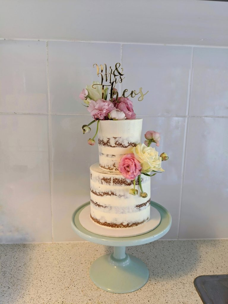 2 tier semi naked buttercream cake with fresh florals