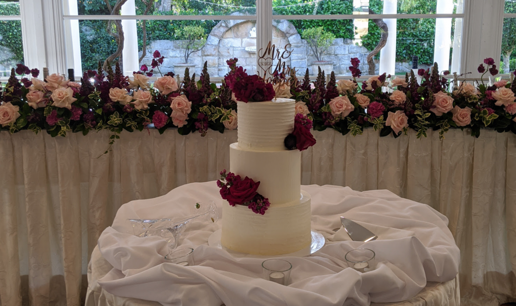3 tiered textured buttercream wedding cake with burgundy flowers