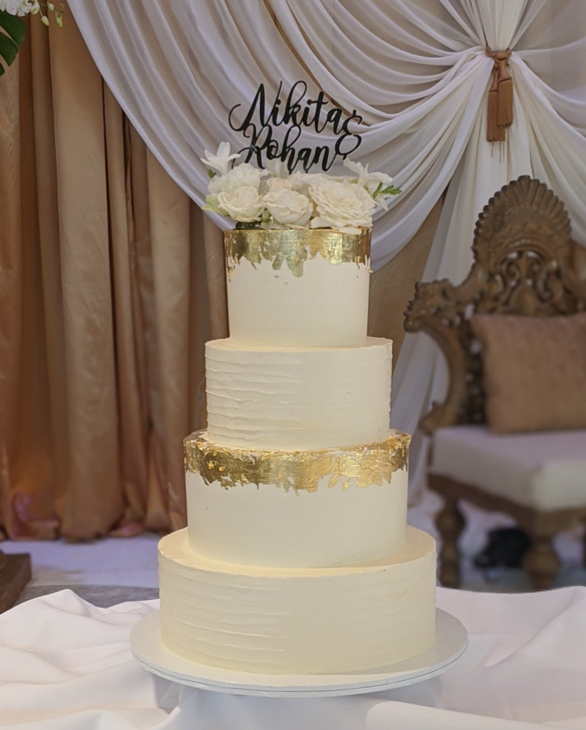 4 tiered buttercream cake with gold leaf and florals