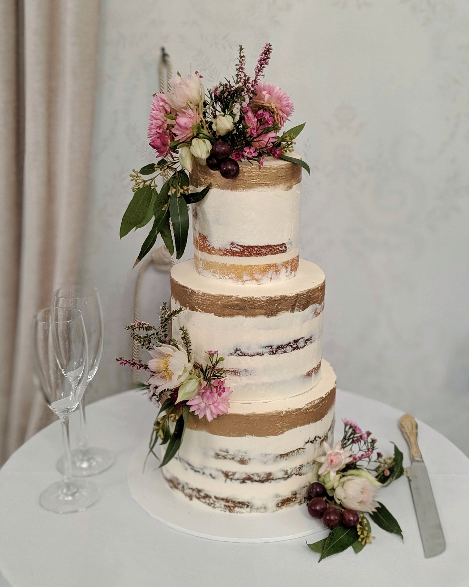 3 tiered semi naked wedding cake with gold detailing and native flowers